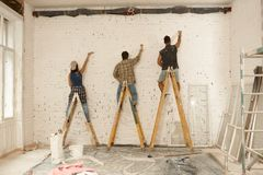 Painters working on renovation site. Painter team working on renovation site, standing on ladder, painting wall by brush Royalty Free Stock Photography