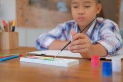 painti asiático del dibujo de brocha de la tenencia del colegial del niño del muchacho del niño imagenes de archivo