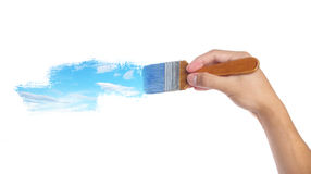 Painting. Hand with paintbrush painting sky isolated on white background Royalty Free Stock Photography