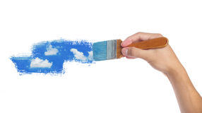 Painting. Hand with paintbrush painting sky isolated on white background Royalty Free Stock Images