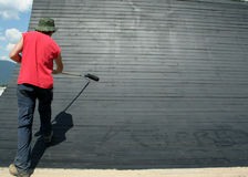 Painting. A painter puts a coat of black paint on a stunt in a mountain bike park. The blank space could be used for advertising royalty free stock photos