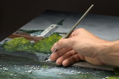 Painting. Hand with paintbrush paintig with white color Royalty Free Stock Photos