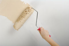 Painting. Hand painting with roller on white wall Stock Photos