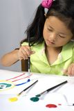 Painting 2. A young girl creates a self portrait with paint stock photos