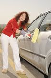 Painting. Elderly Woman Paints The Grey Car With a Roller Royalty Free Stock Image