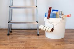 Painting accessories and roller painting equipment.Interiors renovation concept. Painting equipment tools on a wooden floor stock photos