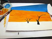 Painting arrid landscape with watercolor. I painted a watercolor landscape: Death Valley - with dry trees and sand dunes royalty free stock images