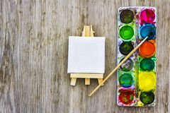 Painting art concept. White miniature easel and multi colored paints with brush on wooden desk. Painting art concept. White miniature easel and multi colored royalty free stock images