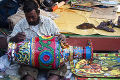 The painting of an artist. Artist painting a beautiful clay pot in a local art fair in bengal, India Stock Image