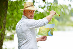 Painting artist with picture in nature Royalty Free Stock Photo