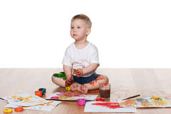 Painting baby boy. A baby boy paints sitting on the floor Royalty Free Stock Images