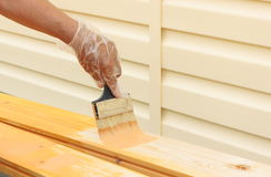 Painting bare wood. Hand with paintbrush Royalty Free Stock Image