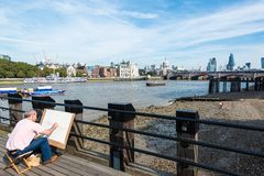 Painting the beauty of London. LONDON, UK - SEPTEMBER 28, 2014: An artist on the South Bank of river Thames is painting the skyline from Saint Pauls Cathedral up stock photos