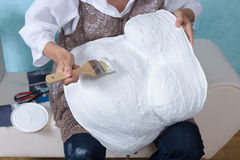 Painting a belly cast. Woman painting a pregnancy belly cast with white primer, to enable decorating Royalty Free Stock Photography