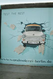 Painting on the Berlin Wall. Restored painting on the Berlin Wall showing a Trabant breaking through the wall royalty free stock photo