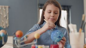 Art Painting of Earth Globe by Creative Child at Home for Hobby Concept. Painting of Blue Ball by Small Person. Paintbrush in Hand of Pretty School Pupil stock footage