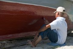 Painting a Boat. A man slowly painting the hull of an old boat stock images