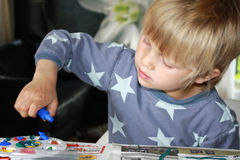 Painting boy. Little boy mixing colours on a painting board Royalty Free Stock Photography