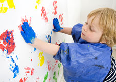 Painting boy. A boy finger painting with blue acrylic paint on a wall stock image