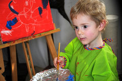 Painting boy. Four years old  toddler boy painting at easel in an art studio Stock Images