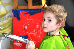 Painting boy. Four years old  toddler boy painting at easel in an art studio Royalty Free Stock Photo