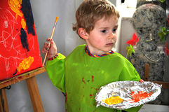Painting boy. Four years old  toddler boy painting at easel in an art studio Stock Photo