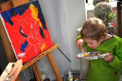 Painting boy. Four years old  toddler boy painting at easel in an art studio Stock Photography