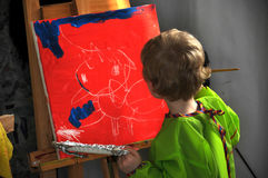 Painting boy. Four years old  toddler boy painting at easel in an art studio Royalty Free Stock Image