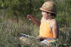 A painting boy. A boy painting at nature stock photo