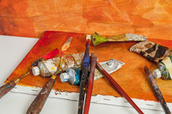 Painting brush and a palette knife on orange canvas desk.  royalty free stock images