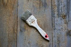 Painting brush in white paint dye is lying on the wooden background. Realistic grey and brown vintage surface. Shaggy and grained. Rough background for working royalty free stock images
