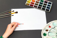 Painting brush on a white sheet. Man painting brush on a white sheet next to a set of drawing Stock Photography
