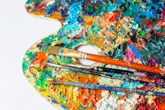 Painting brushes on a colorful palette royalty free stock photography