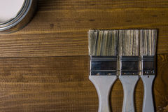 Painting brushes near a metal jar with white paint on an oak table Royalty Free Stock Images