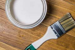 Painting brushes near a metal jar with white paint on an oak table Stock Image