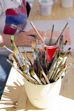 Painting with brushes. Paintbrushes on the table, painting activity in the background Royalty Free Stock Images