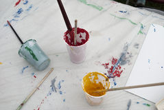 Painting brushes and paints on worktable Royalty Free Stock Image