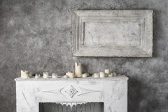 Painting and burnt candles at the fireplace Stock Image
