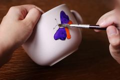 Painting butterfly. Artist paint colorful butterfly on cup stock image