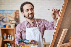 Painting on canvas. Male artist painting on canvas royalty free stock image
