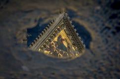 Painting on Cattedrale Metropolitana di Santa Maria Assunta in Siena seen as a reflection in a rain pool stock photos