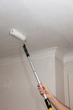 Painting Ceiling. Decorator using extension pole and roller to paint a ceiling stock image