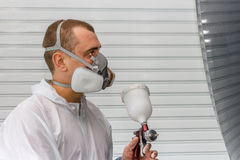 In Painting chamber. The man in protective clothes is going to paint part of a body of the car Royalty Free Stock Photography