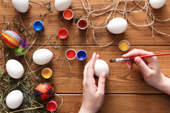 Painting colorful easter eggs, top view on wood Royalty Free Stock Photos