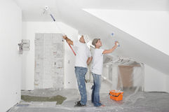Painting. Couple painting walls of apartment Stock Image