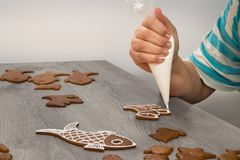 Close-up of a female hand when decorating Christmas gingerbreads royalty free stock images