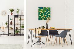 Painting in dining room. Green painting in dining room interior with wooden table, chairs and shelf in the background Royalty Free Stock Photography
