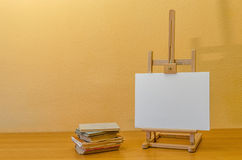 Painting easel with books. Painting easel with few old books on wooden table Stock Photo