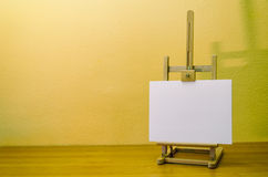 Painting easel with canvas. Small painting easel with canvas on a wooden table Royalty Free Stock Photo