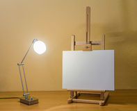 Painting easel with lamp. Wooden painting easel and a lit modern lamp on wooden table Stock Image